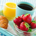Breakfast with strawberries, orange juice, egg, croissant and coffee, on blue table cloth vintage background
