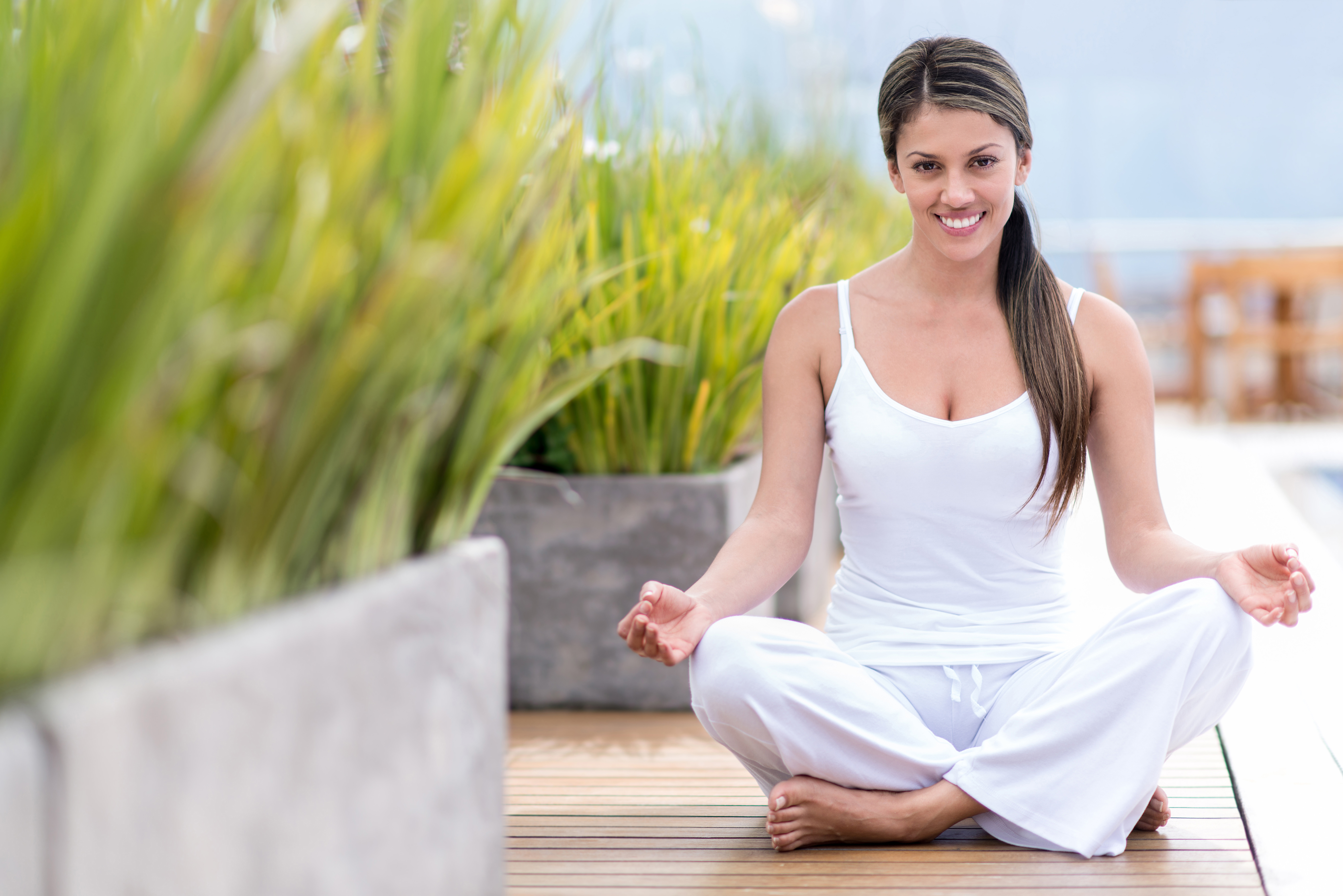 Yoga woman sitting on the floor and smiling outdoors